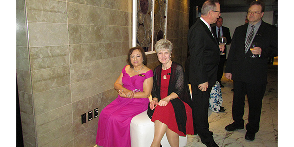 Hilda Pacey, wife of Larry Pacey, chats with Debbie Odom, wife of Tim Odom, CEO of AAM Parts Pro at the cocktail reception.